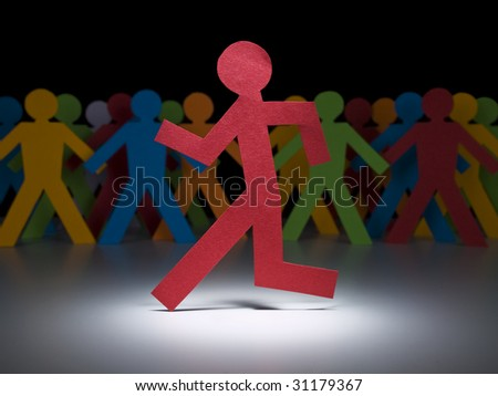 A red paper figure runs under the spotlight in front of a multicolor crew. - stock photo