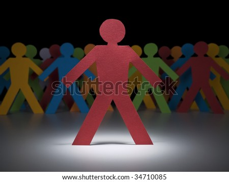 A red paper figure stands under the spotlight in front of multicolor crew. - stock photo