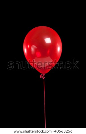 A red party balloon on a black background - stock photo
