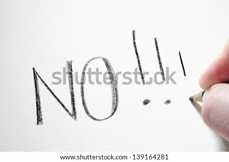 A red pencil is smash on a piece of paper after writing the word 'NO'. - stock photo