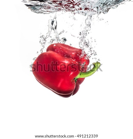 A red pepper being dropped into clear water