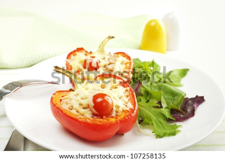 A red pepper halved and stuffed with rice, tuna and tomatoes, topped with cheese, and baked. - stock photo