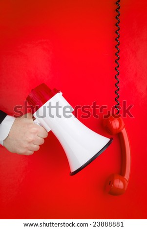 A red phone and a megaphone in front of a red wall. - stock photo