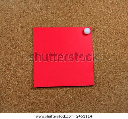 A red piece of paper pinned to a corkboard. - stock photo