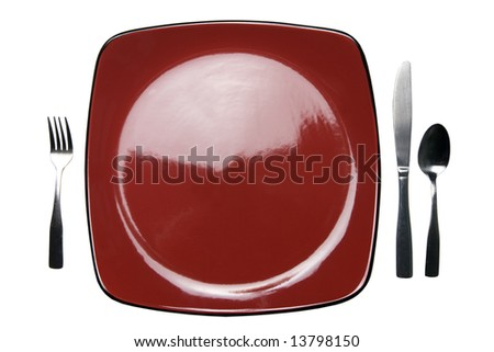 A red plate with knife, fork and spoon. Isolated on white with a clipping path. - stock photo