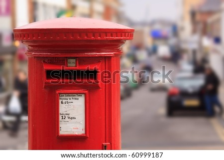 A red post box set against a de-focused city centre background - stock photo