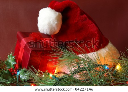 A red present and santa hat in a nice Christmas season setting.