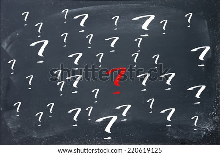 A red question mark and many white question mark on blackboard - stock photo