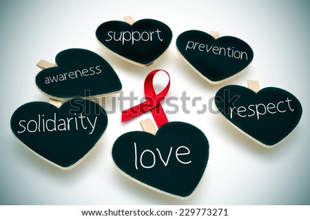 a red ribbon for the fight against AIDS and some heart-shaped blackboards with words such support, prevention, respect, love, solidarity and awareness - stock photo