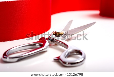 A red ribbon with a pair or shiny silver ceremonial scissors or sheers - stock photo