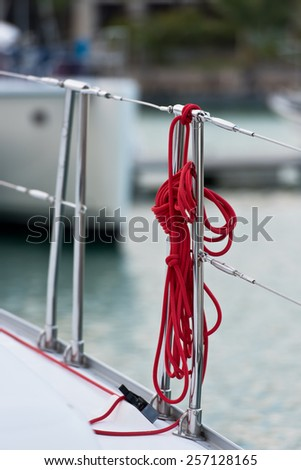 A red rope tied around a lifeline. Vertical shot - stock photo
