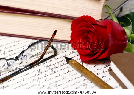 A red rose lays on top of a hand written document with a pile of books behind. - stock photo
