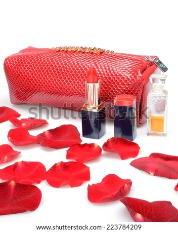 A Red rose petals, cosmetic bag female cosmetics, perfumery in still life - stock photo