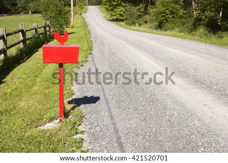 A red Royal Mail post box on a post in a country location - stock photo