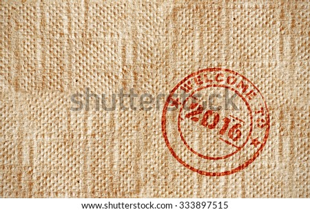 A red rubber stamp with text Welcome to 2016 on a grungy brown serviette paper. - stock photo