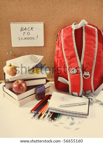 A red school back pack or book bag overflowing with school supplies - stock photo