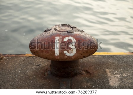 a red ship bollard by the dock with the number 13 painted on it - stock photo