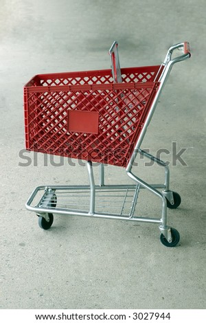 A Red shopping card isolated on a platform - stock photo