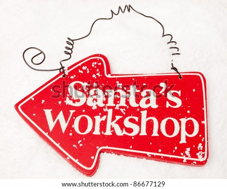 A red sign showing the way to santas workshop sat in snow - stock photo