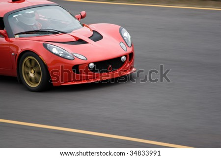A red sports car speeding down the road. - stock photo