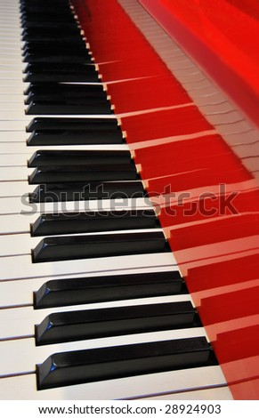 A red Steinway grand piano with ebony and ivory keys reflected on the glossy lacquer paint surface and fading into the distance. - stock photo