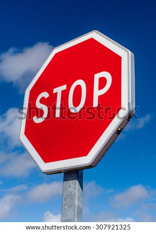 A red stop sign against a deep blue sky