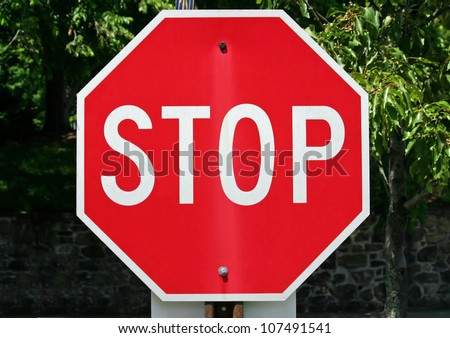 A red stop sign with trees in the background - stock photo