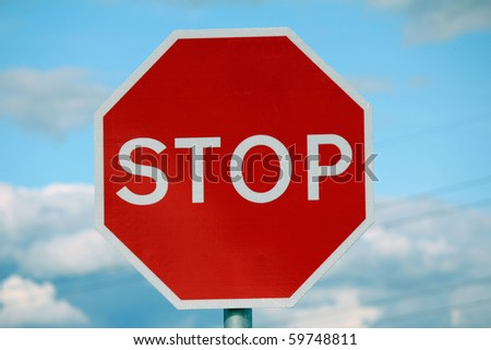 A red stop warning road sign with cloudy and blue sky background with clipping path around pole and sign - stock photo