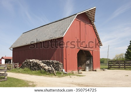 A red storage barn with an opened barn door on a bright, sunny day.  Stacks of wood leans against one side, a distant barn and rail fences on all sides, near and far. - stock photo