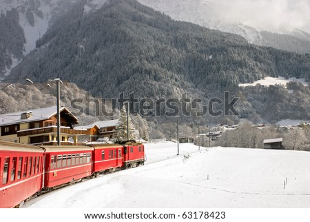 A red swiss train running through the snow. - stock photo