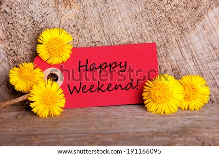A Red Tag with the Words Happy Weekend on it and Yellow Flowers on Wood - stock photo