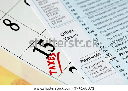 A red tax mark on date of 15th and tax form, close up - stock photo