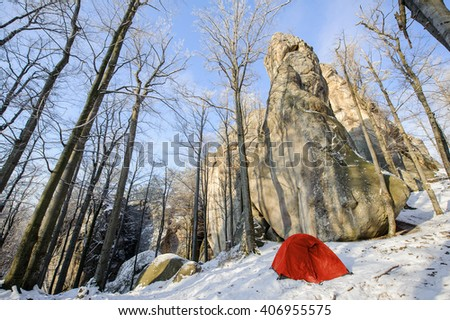 A red tent standing on the snow next to rocky cliff during an extreme winter climbing adventure - stock photo