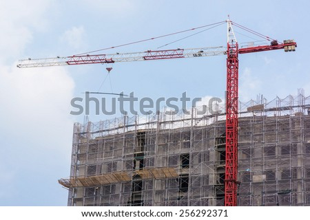 A Red Tower Crane Lifting Steel Bars by A Constructing Building  - stock photo