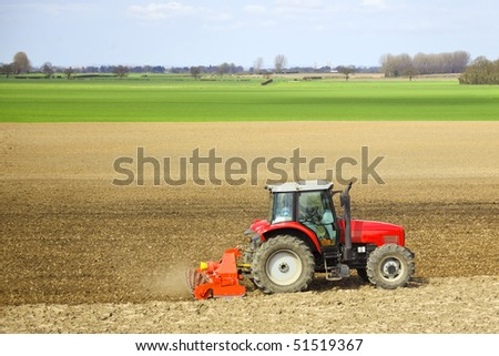 a red tractor cultivating a field in springtime with green grass and blue sky - stock photo