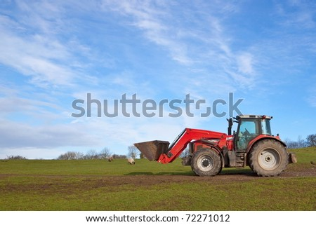 a red tractor parked on a grassy hillside under a blue sky with streaked clouds