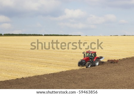 a red tractor plowing a stubble field in summer on a hillside under a cloudy sky - stock photo