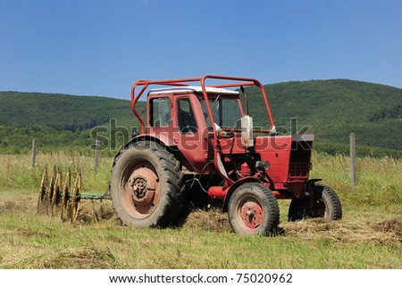 A red tractor pulls a hay rake