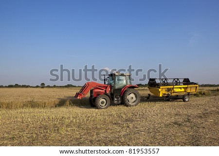 a red tractor with the cutting head of a combine harvester on a yellow trailer under a blue sky at harvest time
