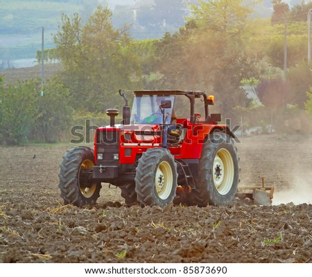 A red tractor working on a field - stock photo