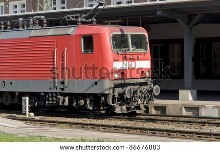 a red train in front of a station in Southern Germany