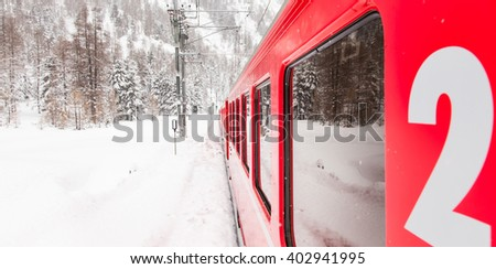 A red train in the middle of a desert of snow - stock photo