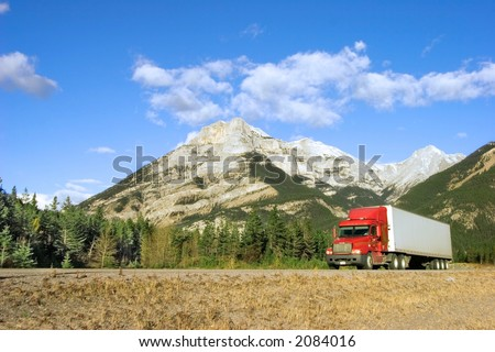 a red truck goes through the canadian rockies - stock photo