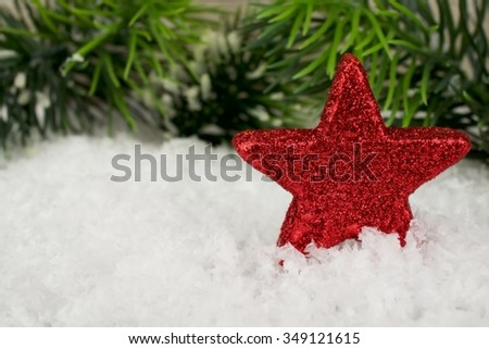 A red twinkling star in the snow with fir branch in the background - stock photo