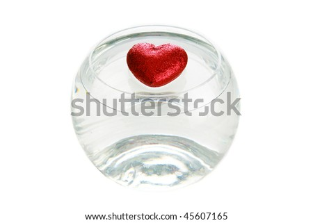 a red valentines day heart floats in water in a fish bowl - stock photo