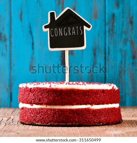 a red velvet cake with a chalkboard in the shape of a house with the text congrats, on a rustic blue wooden surface, with a retro effect - stock photo