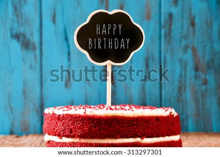 a red velvet cake with a chalkboard in the shape of a thought bubble with the text happy birthday, on a rustic blue wooden surface, with a retro effect - stock photo