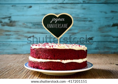 a red velvet cake with a heart-shaped chalkboard with the text joyeux anniversaire, happy birthday in french, on a rustic wooden table - stock photo