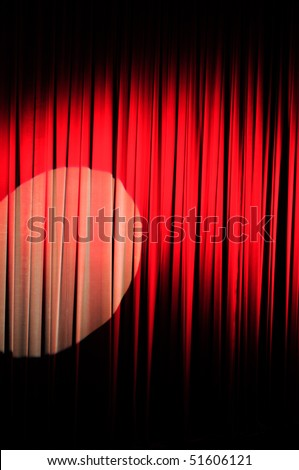 A red velvet stage curtain with a spotlight on it for effect.  Part of a series - stock photo