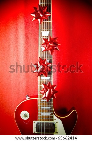 A red vintage solid body electric guitar with red ribbon bows on fretboard. A concept image for Christmas and holiday season music event. - stock photo